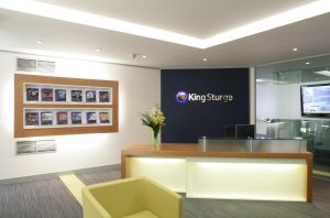 Wrap Around Wood Veneer Reception Desk with LED Underlighting - King Sturge - Colinton Furniture